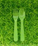 绿色匙子和叉子在绿色草坪 免版税库存照片