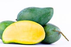 绿色半在白色被隔绝的背景健康果子食物的芒果被剥皮的和三个新鲜的绿色芒果 免版税图库摄影