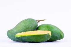 绿色半在白色被隔绝的背景健康果子食物的芒果被剥皮的和两个新鲜的绿色芒果 图库摄影