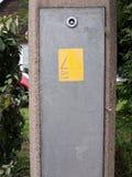 黄色危险的载电线和在a的黑紧急警报信号 免版税库存图片