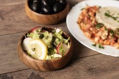 绿色卷心莴苣沙拉用黄瓜、萝卜、向日葵种子、柠檬和巴马干酪 后面,在defokus鸡用米 库存图片