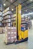 黄色叉架起货车司机在仓库里经营, 库存照片