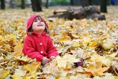 黄色叶子的一个小女孩 秋天 库存照片