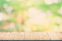 绿色叶子bokeh迷离和木头桌 免版税图库摄影