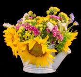 黄色向日葵和色的野花在一个白色喷水隆头,关闭黑背景 免版税库存照片