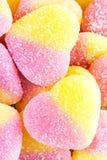 黄色和桃红色果子糖果背景在心脏,克洛形状的  免版税库存照片