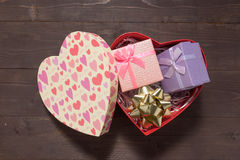 紫色和桃红色礼物盒在红色心脏箱子,在木b 免版税图库摄影