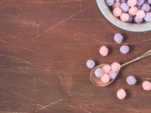 紫色和桃红色糖果在木背景滚保龄球 图库摄影
