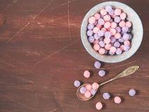 紫色和桃红色糖果在木背景滚保龄球 免版税库存照片