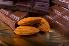 黑色和牛奶巧克力与坚果在箔 图库摄影