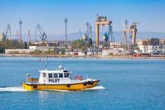 黄色和白色小领航船进入口岸 免版税图库摄影