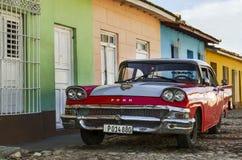 紫色和白色经典美国汽车和蓝色殖民地大厦在特立尼达,古巴的街道 库存图片