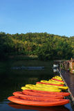 黄色和红色皮船有森林和蓝天背景 免版税图库摄影
