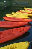 黄色和红色皮船的样式在黑暗的水的 库存图片