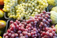 绿色和红葡萄在水果市场上 免版税库存图片