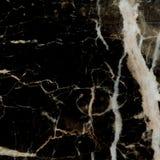 黑色和金子大理石被仿造的纹理背景 库存照片