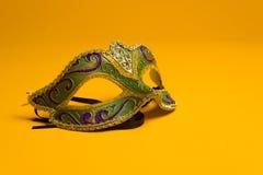 绿色和金子狂欢节,在黄色背景的威尼斯式面具 免版税库存照片