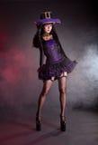 紫色和黑哥特式万圣夜服装的性感的巫婆 免版税库存图片