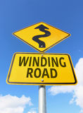 黄色和黑弯曲道路标志和箭头 免版税图库摄影