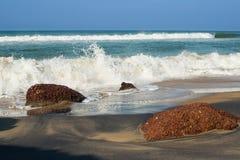 黑色和黄沙与打破在一个石海滩的波浪 图库摄影