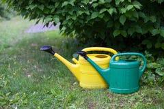 黄色和绿色喷壶在庭院里 免版税库存照片