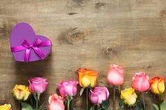 紫色和黄色玫瑰,把在木背景的礼物装箱 库存照片