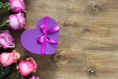 紫色和黄色玫瑰,把在木背景的礼物装箱 免版税库存照片