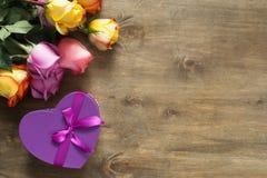 紫色和黄色玫瑰,把在木背景的礼物装箱 免版税库存图片