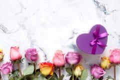 紫色和黄色玫瑰,把在白色背景的礼物装箱 免版税库存图片