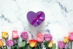 紫色和黄色玫瑰,把在白色背景的礼物装箱 免版税库存照片
