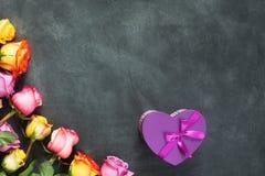 紫色和黄色玫瑰,把在黑背景的礼物装箱 库存图片
