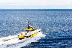 黄色和黑领航船切口通过大海 免版税库存照片
