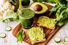 绿色圆滑的人和两个三明治用鲕梨 健康素食主义者食物 库存照片