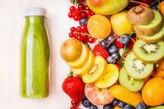 绿色圆滑的人或汁液用各种各样的果子和莓果成份在白色木背景 库存图片