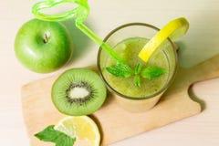 绿色圆滑的人用苹果、猕猴桃、柠檬和薄菏 免版税库存照片