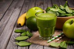 绿色圆滑的人用苹果、香蕉、鲕梨和菠菜在木土气背景 免版税库存照片