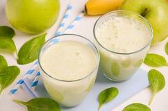 绿色圆滑的人用苹果、香蕉和菠菜在白色背景 免版税库存照片