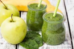 绿色圆滑的人用苹果、香蕉和菠菜在轻的背景 免版税图库摄影