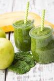 绿色圆滑的人用苹果、香蕉和菠菜在轻的背景 图库摄影
