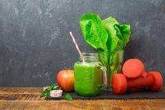 绿色圆滑的人用苹果、莴苣和哑铃在黑暗的背景 戒毒所,节食,素食主义者,健身或者健康吃 免版税库存图片