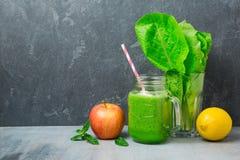 绿色圆滑的人用苹果、莴苣和柠檬在黑暗的背景 戒毒所,节食,素食主义者或者健康吃 免版税库存图片