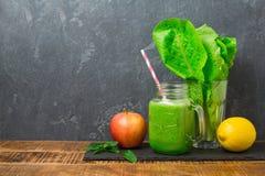 绿色圆滑的人用苹果、莴苣和柠檬在黑暗的背景 戒毒所,节食,素食主义者,健身或者健康吃 免版税库存照片
