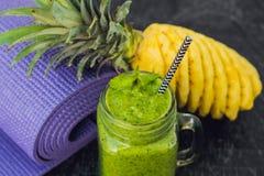 绿色圆滑的人由菠菜制成和菠萝和瑜伽席子 健康吃和体育概念 库存照片
