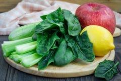 绿色圆滑的人的成份用芹菜、黄瓜、菠菜、苹果和柠檬 免版税图库摄影
