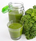 绿色圆滑的人玻璃和瓶子用新鲜的无头甘蓝 免版税库存图片