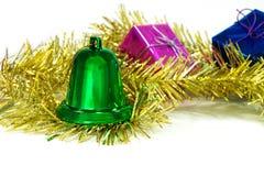 绿色圣诞节铃声在闪亮金属片和礼物盒 库存照片