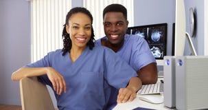黑色在坐在计算机的护士驻地护理 免版税库存照片
