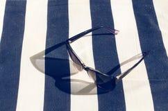 黑色在毯子的被反映的太阳镜 从玻璃的阴影 阳光 背景概念框架沙子贝壳夏天 免版税库存图片