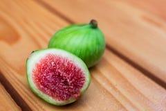 绿色在湿木桌上的切的无花果 免版税库存照片