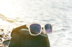 黑色在的被反映的太阳镜石头 从玻璃的阴影 阳光 背景概念框架沙子贝壳夏天 库存图片